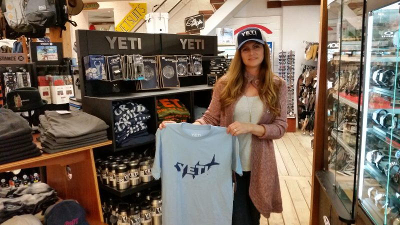 Kim DeMarco, a surf shop salesperson, models some Yeti caps and T-shirts.