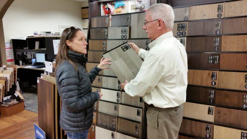 Salesman Rick Marshall shows customer Lisa Baehner a flooring sample.